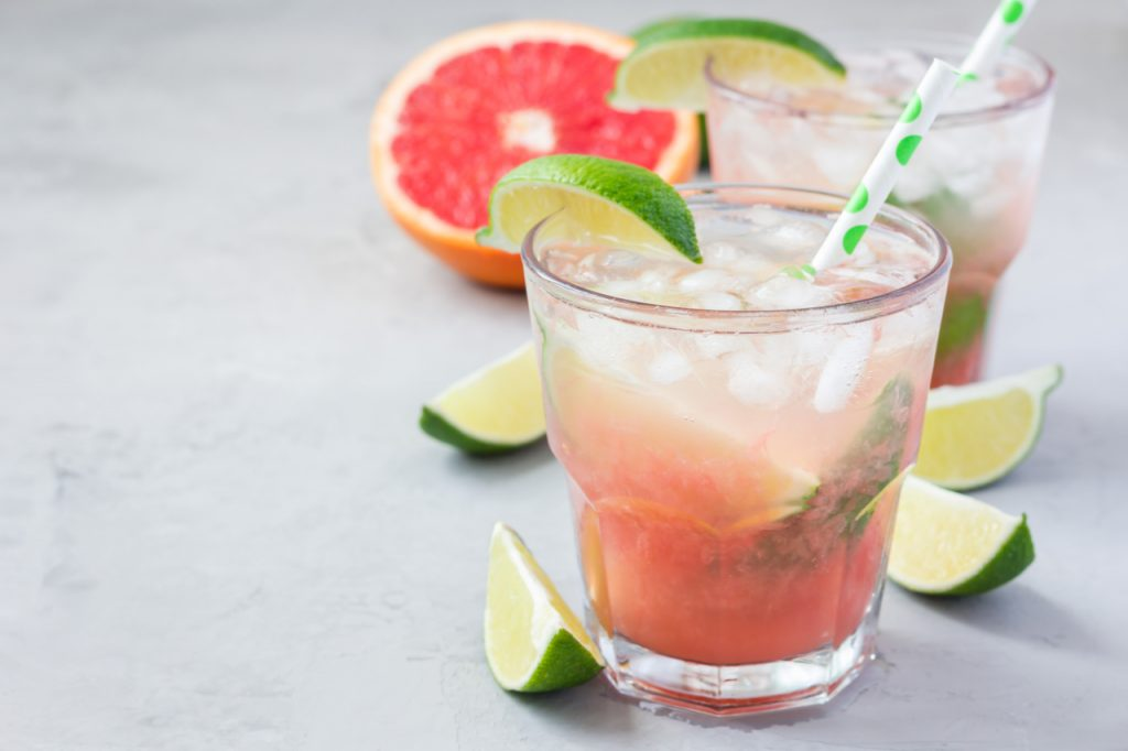 Paloma cocktail with fresh grapefruit, lime and ice cubes on concrete background.