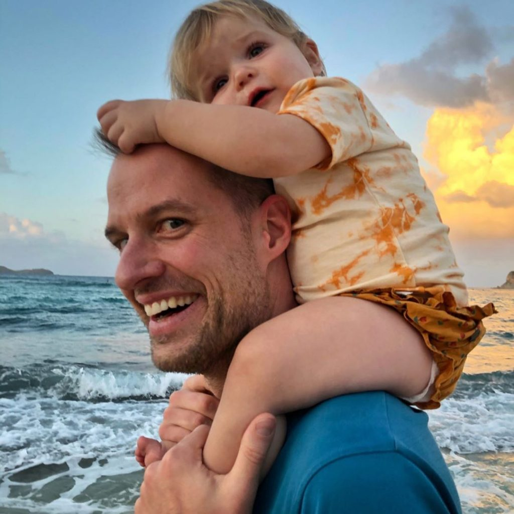 Philippe von Borries at the beach while carrying his daughter Viva on his shoulders.