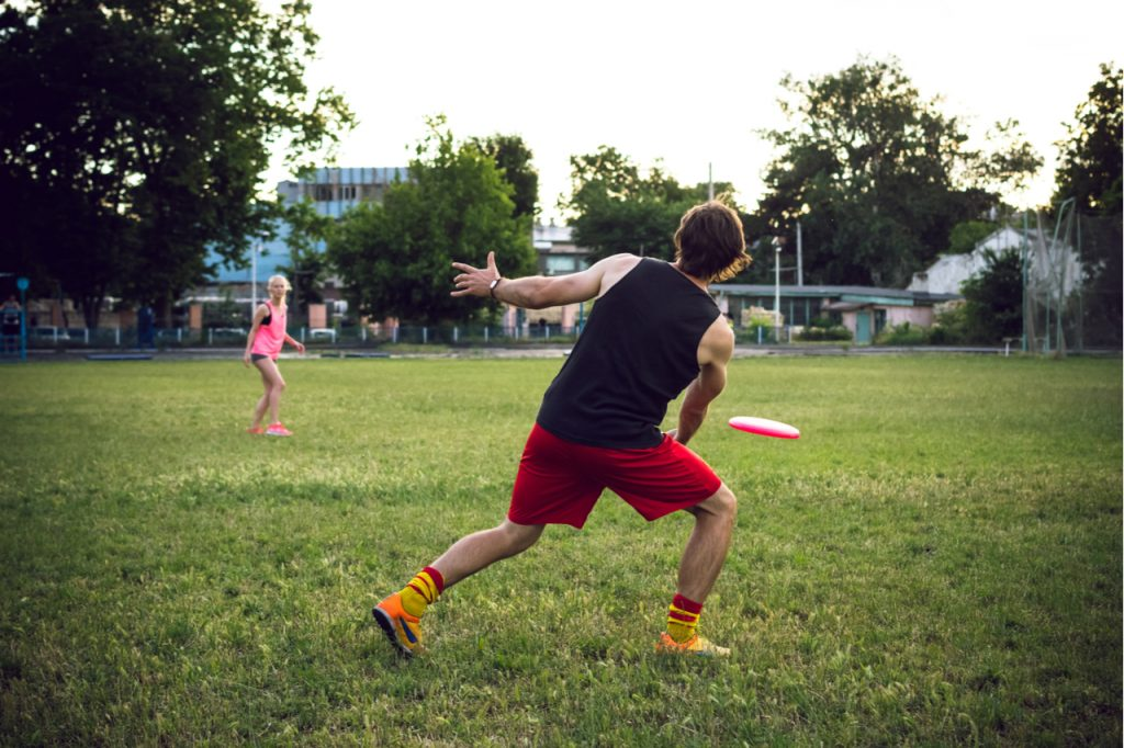 A couple playing ultimate frisbee in a park.