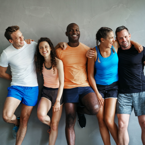 Smiling group of friends in sportswear laughing together while standing arm in arm in a gym after a workout.