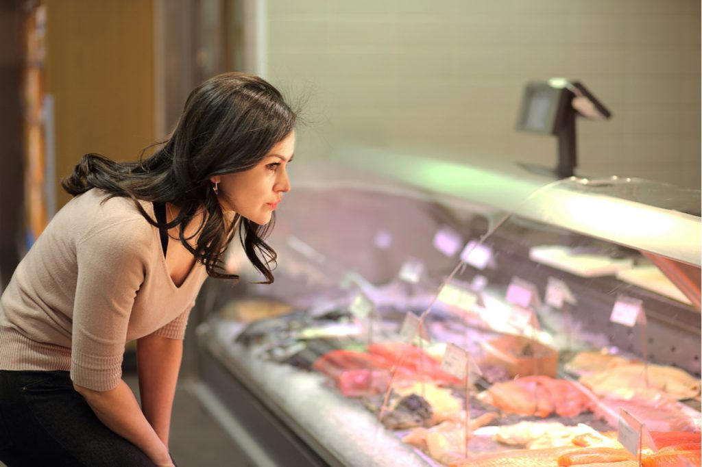 Woman chooses meat in the meat department.