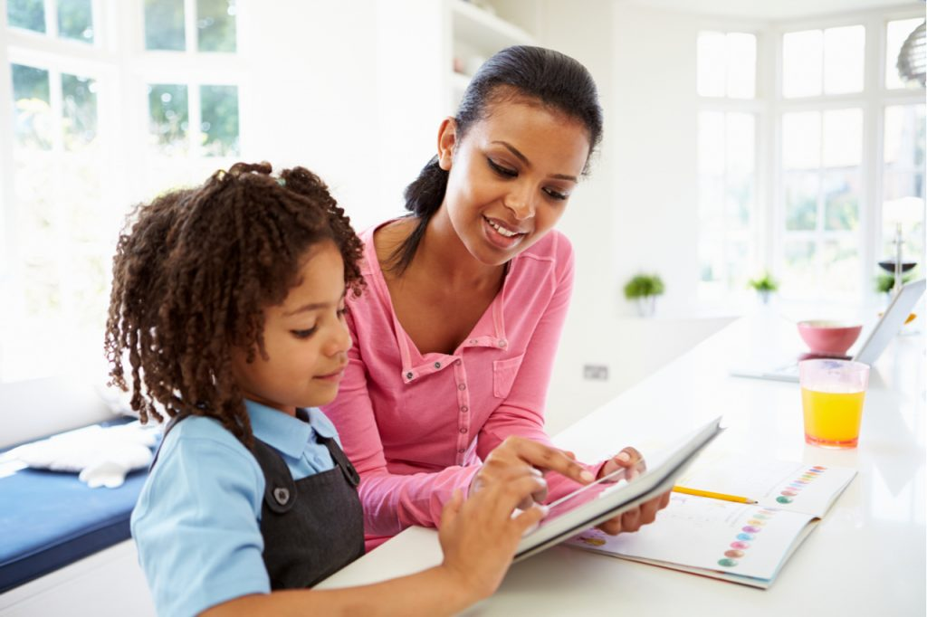Mother And Child Using Digital Tablet For Homework.