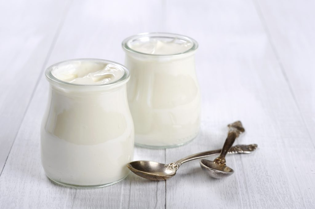 Greek yogurt in a glass jars with spoons on wooden background