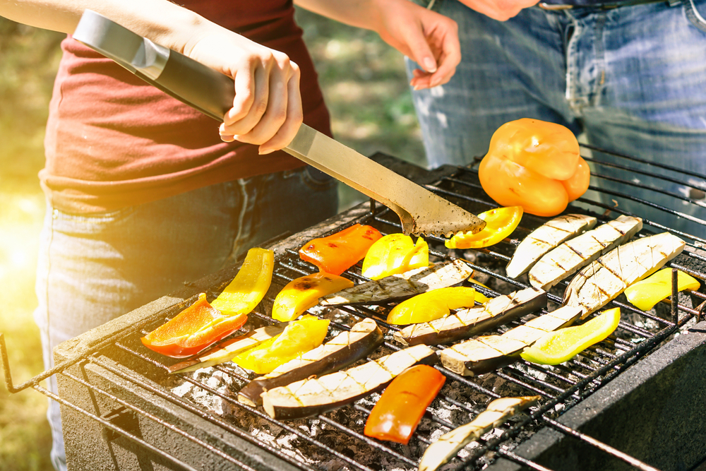 A woman grilling vegetables outdoors.