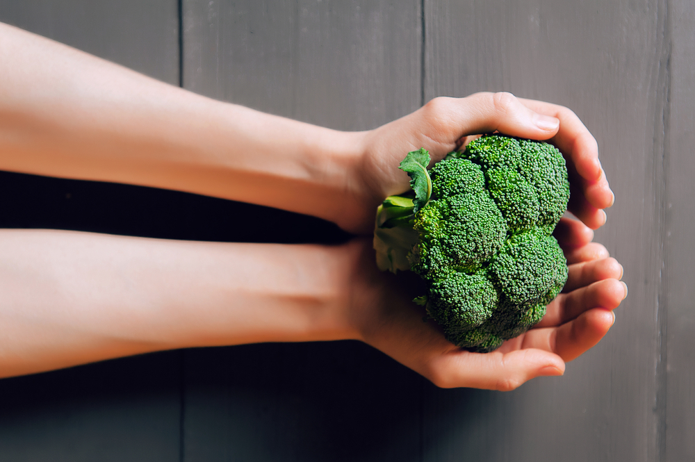 broccoli in hands. a wooden background. healthy eating concept.