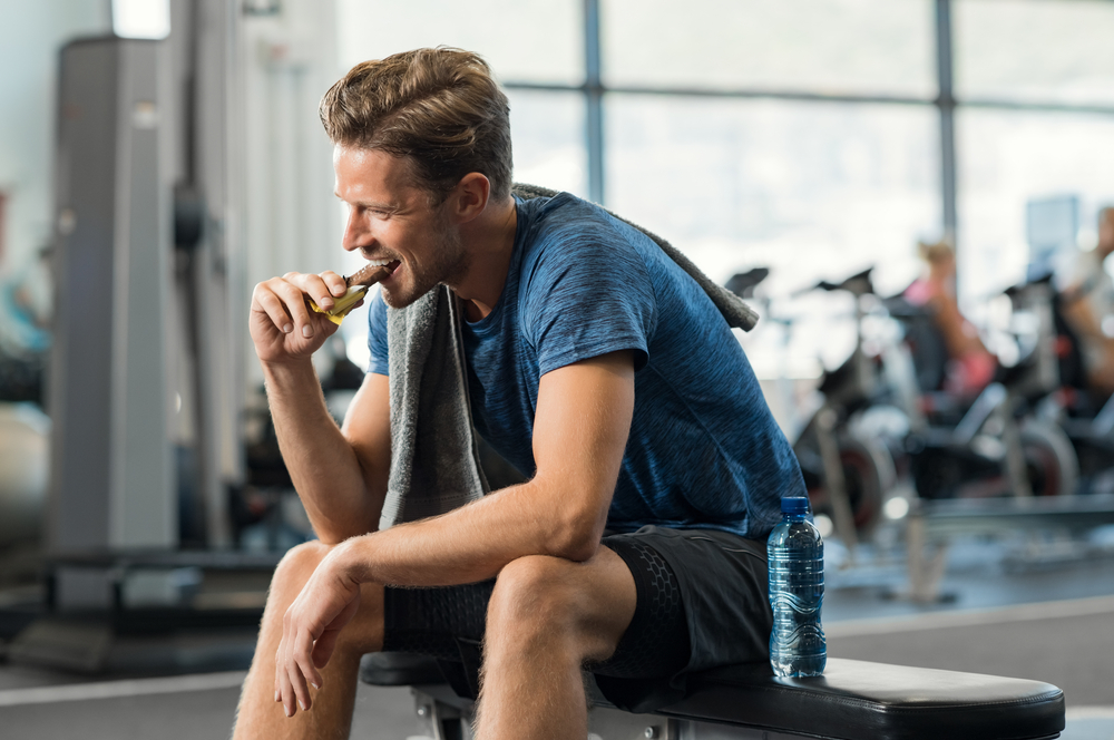 A man sitting in a bench while eating protein bar after working out.
