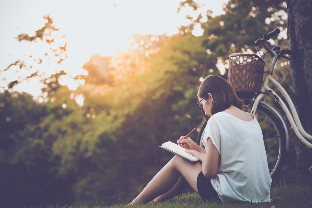 woman writing into her diary, in the park