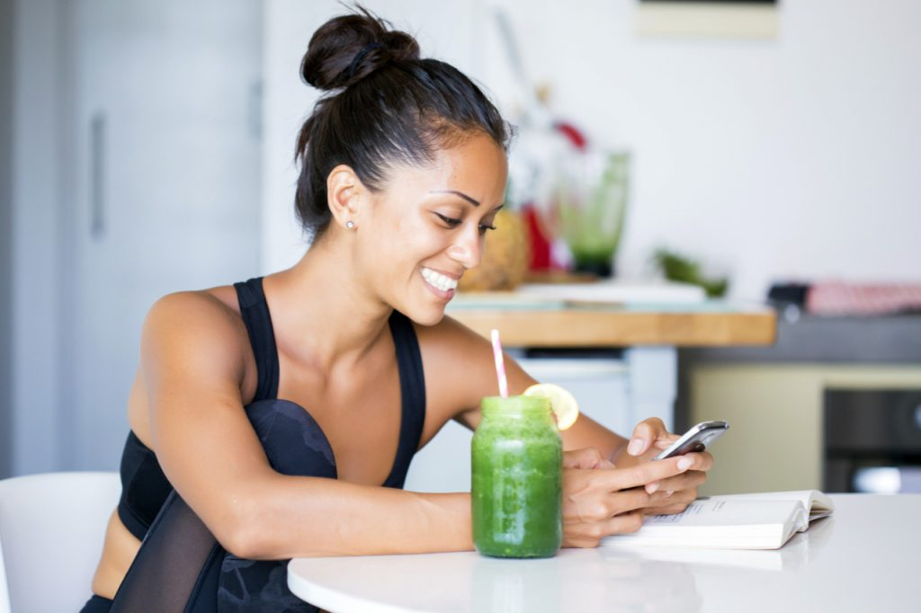 Woman drinking a splendid spoon smoothie, wearing sportive clothing, texting on her phone while sitting in her kitchen table.