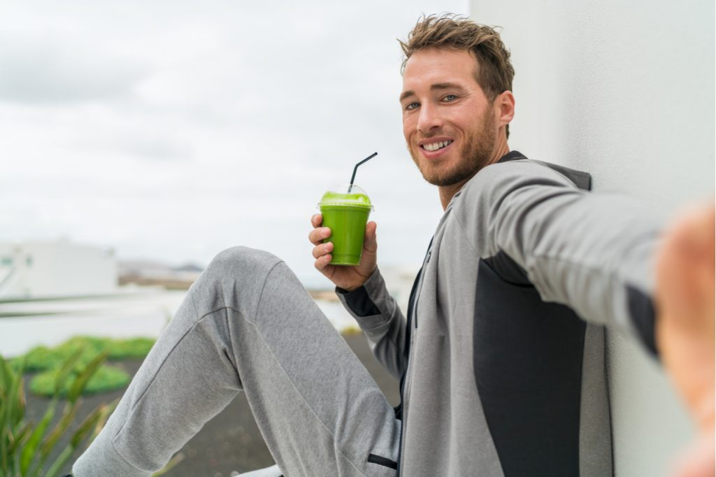 Fitness man taking self portrait picture at gym drinking vegetable juice after workout in sweatpants and sportswear.