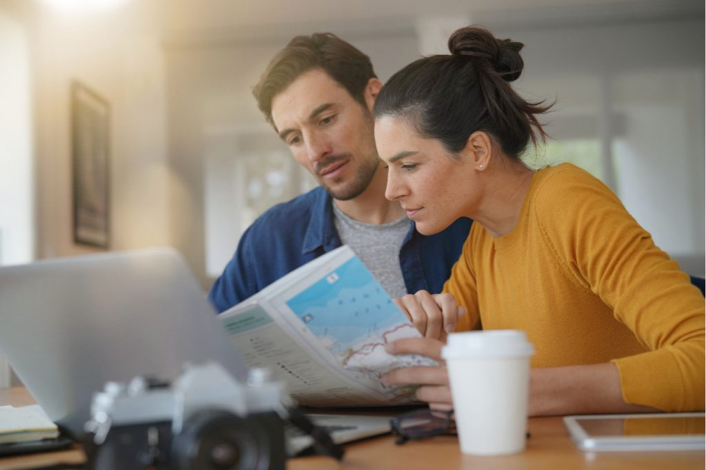 Couple planning their trip looking at map at home.