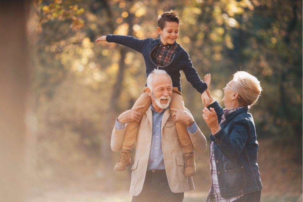 Smiling grandson walking through autumn park with grandparents.