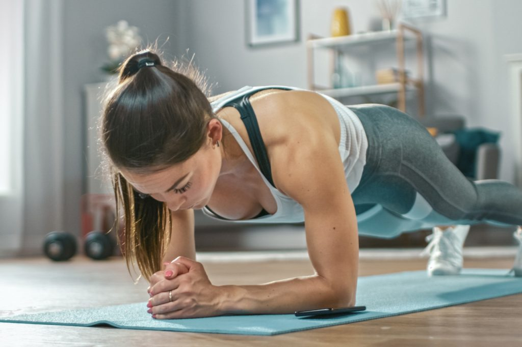 A fit woman doing plank workout at home trying to do the deck of pain workout.