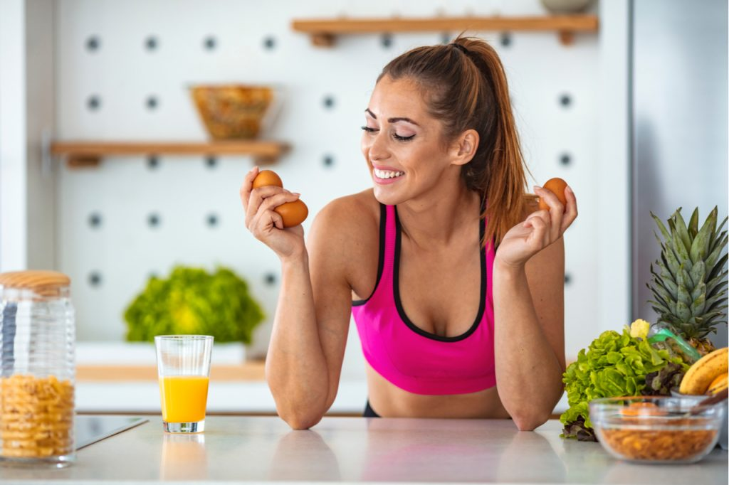 A sporty woman feeling happy to be prepping some eggs before workout.