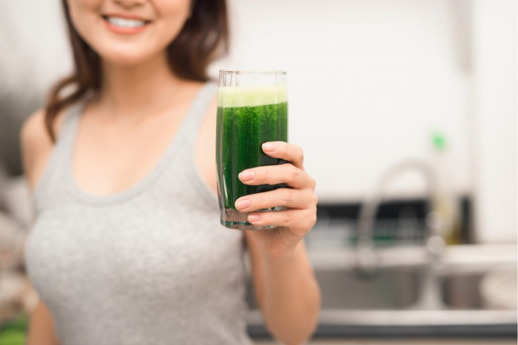 Smiling woman holding a glass of green drink.
