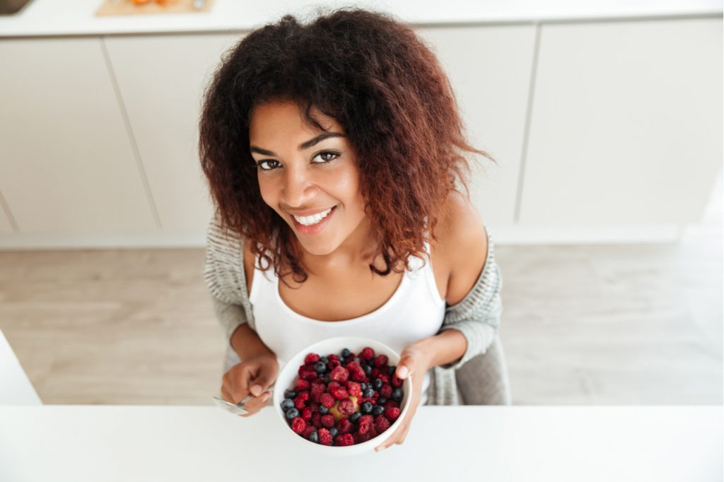 An African American woman holding a bowl of berries.