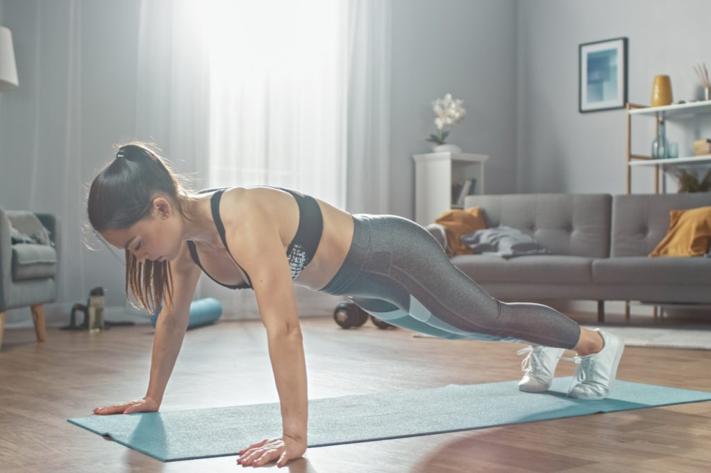 A woman doing push-ups at home trying the deck of pain workout.