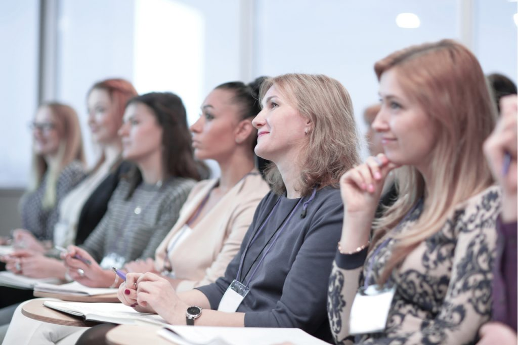 Several women focused on listening and learning in a conference or seminar.