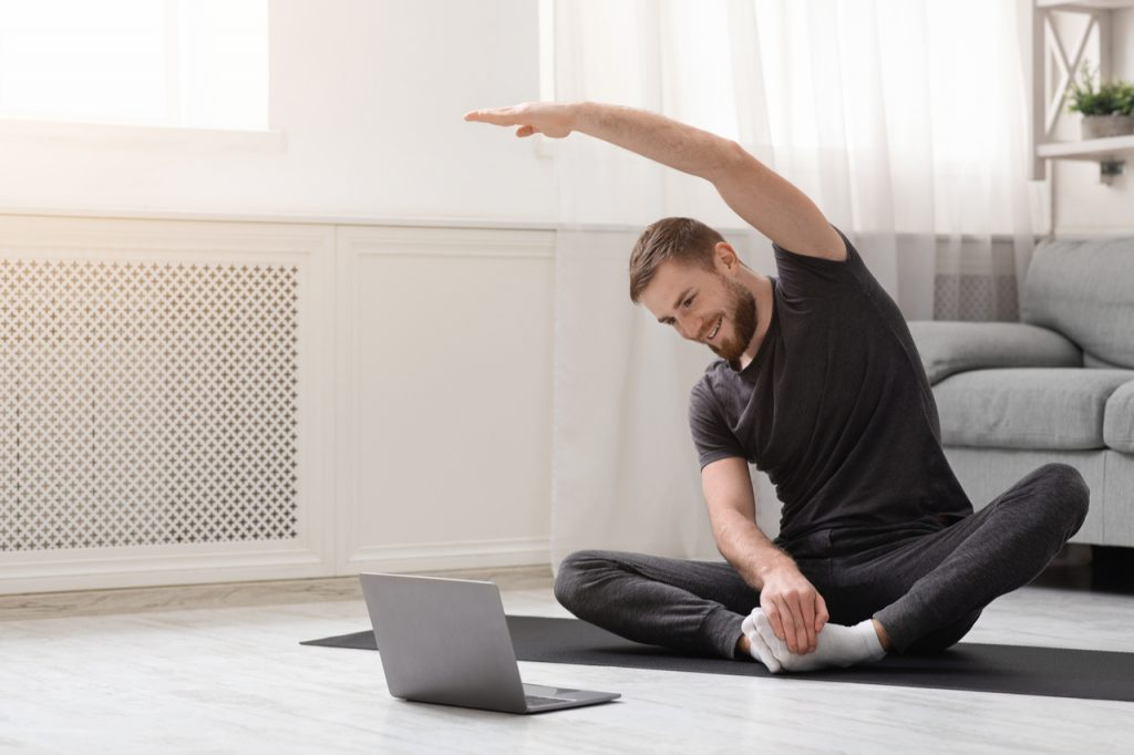 Man practicing yoga at home during an online fitness class.