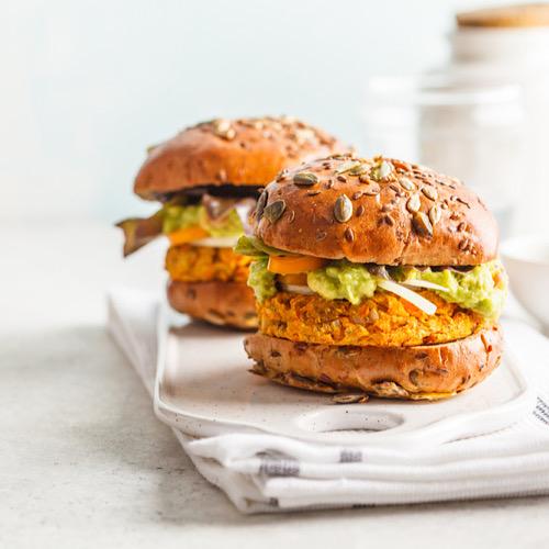 Vegan sweet potato (or pumpkin) burgers on white background.