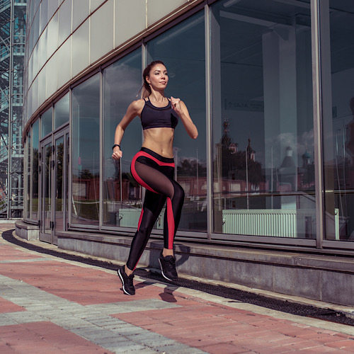 athletic tanned athlete girl run summer city background glass windows,