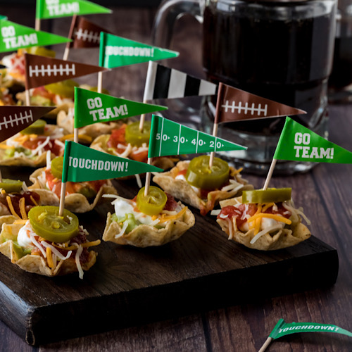 A close up view of a wooden platter of layered dip appetizers topped with jalapenos ready for a Super Bowl party.
