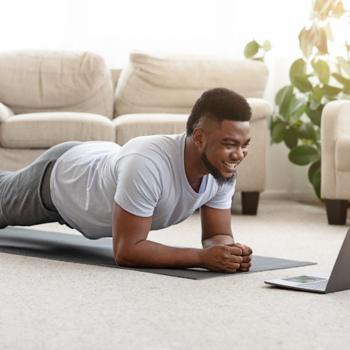 Training At Home. Sporty man doing yoga plank while watching online tutorial on laptop, exercising in living roo