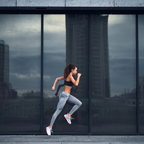 Young athletic woman jumping while making running training at urban city location with big mirror windows on background