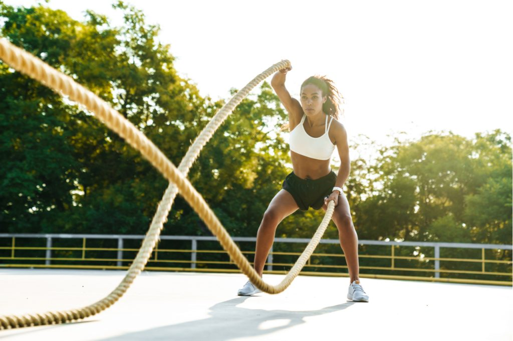 Woman in sportswear doing workout with battle ropes at playground outdoors.