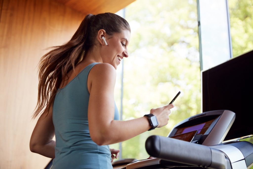 Woman Exercising On Treadmill Wearing Wireless Earphones And Smart Watch Checking Mobile Phone