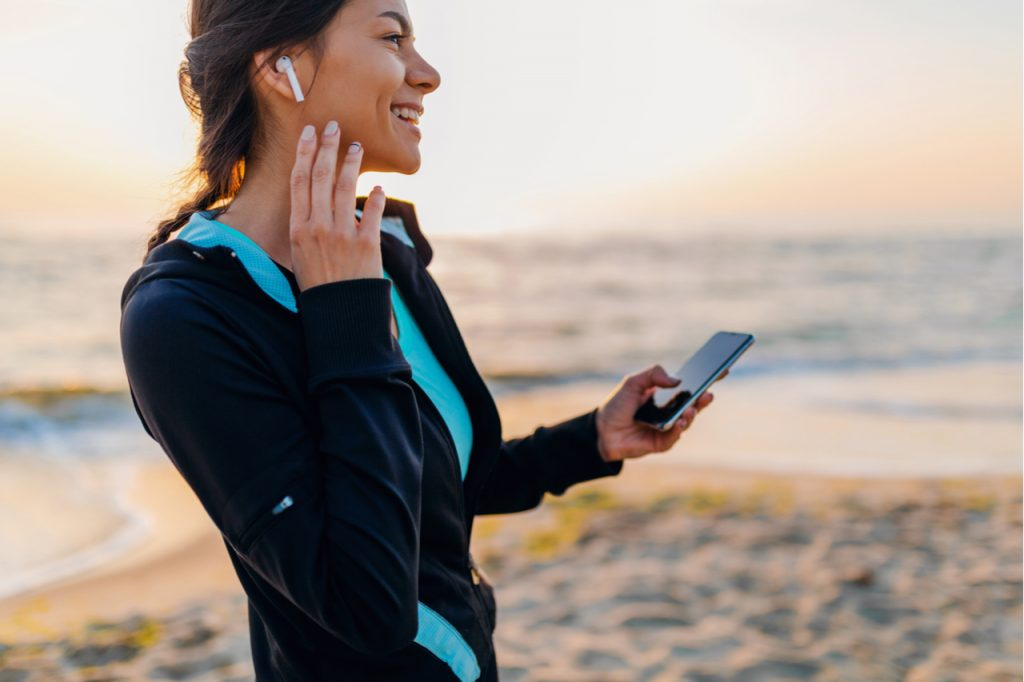 Woman doing sport exercises on morning sunrise beach in sports wear listening to music on wireless earphones holding smartphone.
