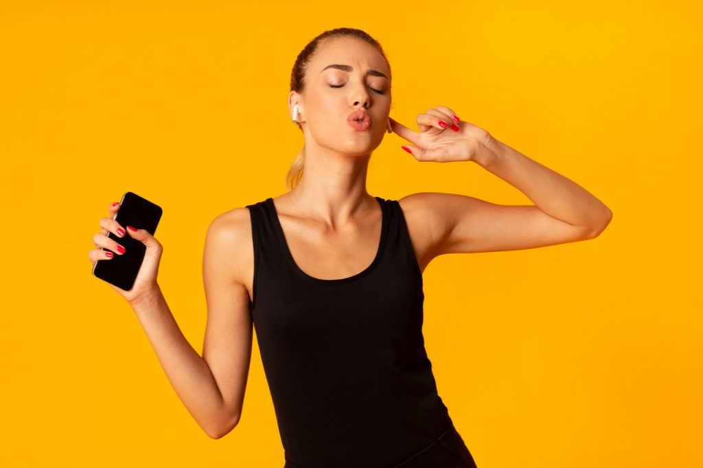 Fitness Lady In Beats by Dr. Dre Powerbeats Pro Wireless Earphones Holding Smartphone Enjoying Music Dancing Over Yellow Studio Background