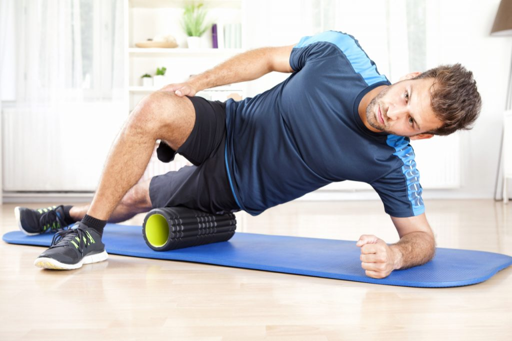 Man Doing Side Planking with Foam Roller on his Thigh.