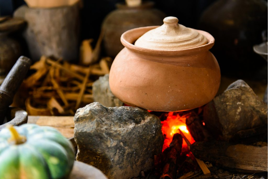 A traditional cooking pot on high flame to boil food.