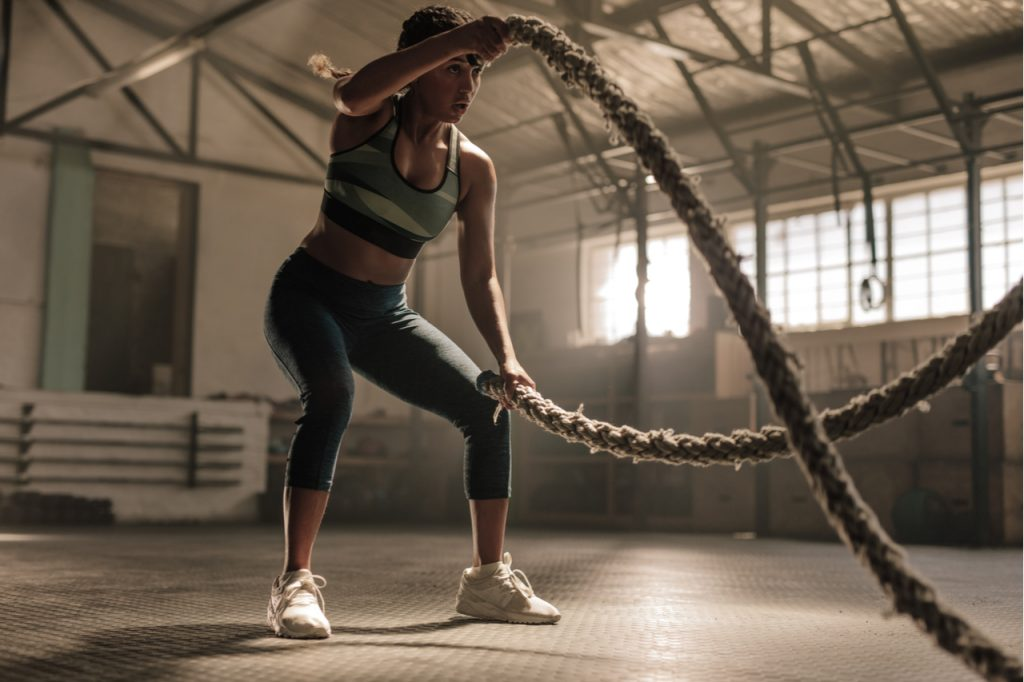 Fitness woman using Bonnlo Battle Ropes for exercise at gym.