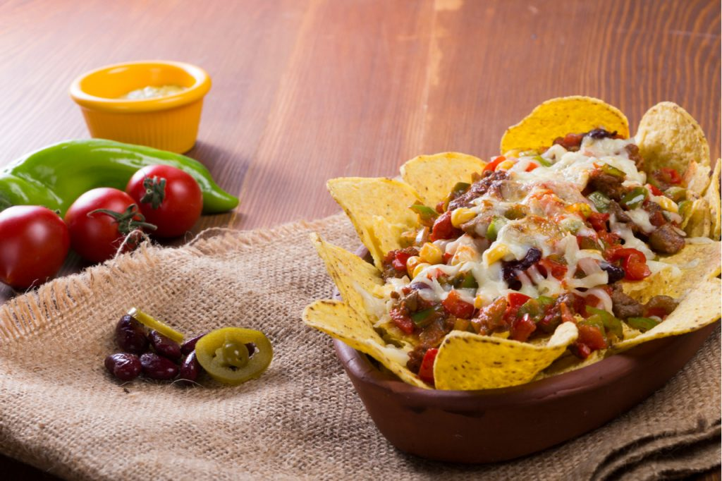 One of the best nacho recipe is chicken Nachos. Baked in casserole with cheese, beans, corn, hot jalapeno, chicken, red pepper and mushrooms serving on wood table.