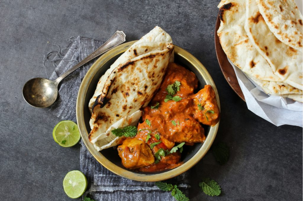 Chicken Tikka Masala, sliced lime and pita bread.