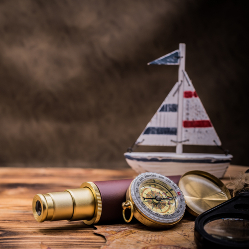 A compass, a miniature boat, and a telescope symbolizing columbus day.