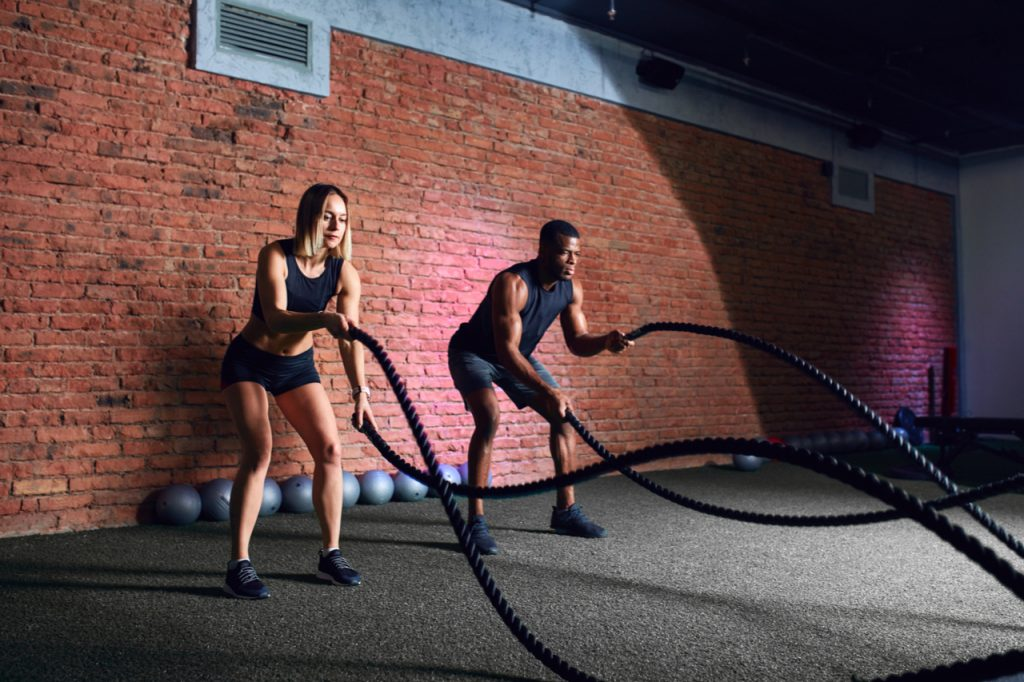 Interracial family couple exercising with Pro Battle Ropes With Anchor Strap Kit.