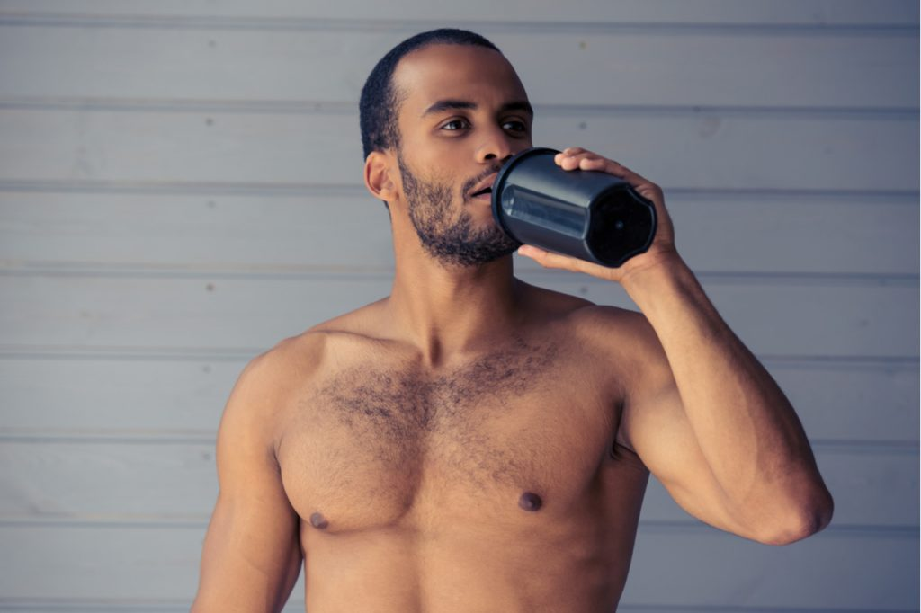 Handsome Afro American sportsman is drinking protein shake while standing topless in front of gray wall.