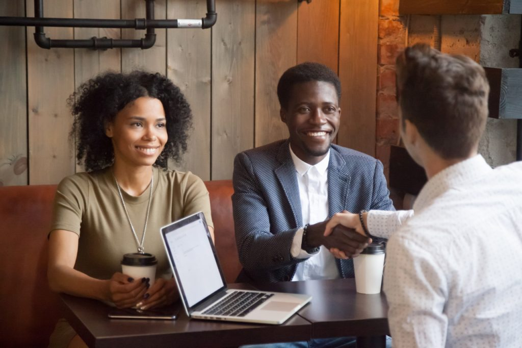 Smiling african american couple shaking hands with their financial advisor.
