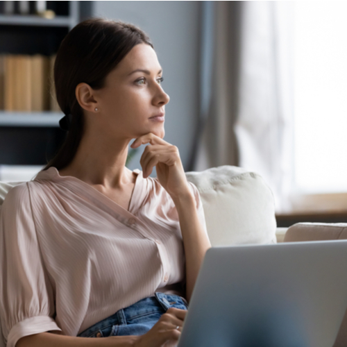 Distracted from work worried young woman sitting on couch with laptop.