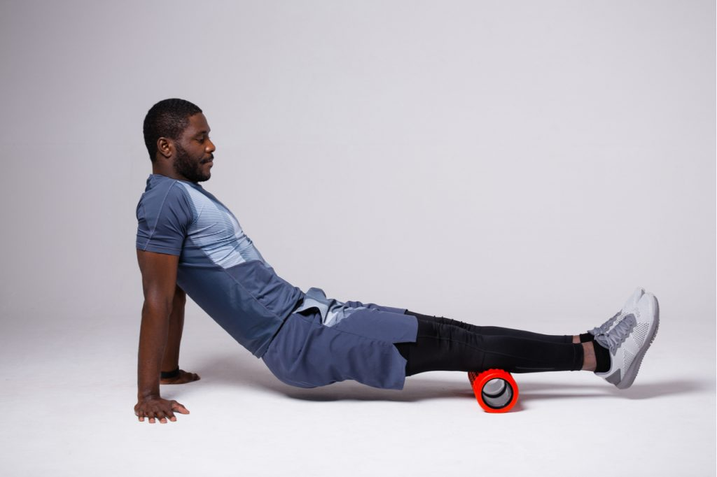 Man exercising with massage roll on white background.