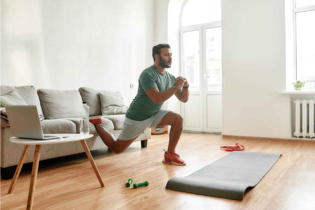 A fit man working out at home with live online session with his trainer.
