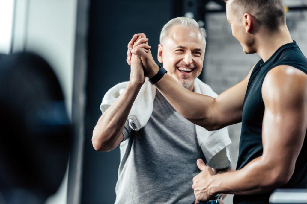 Senior sportsman giving highfive to trainer in sport center.
