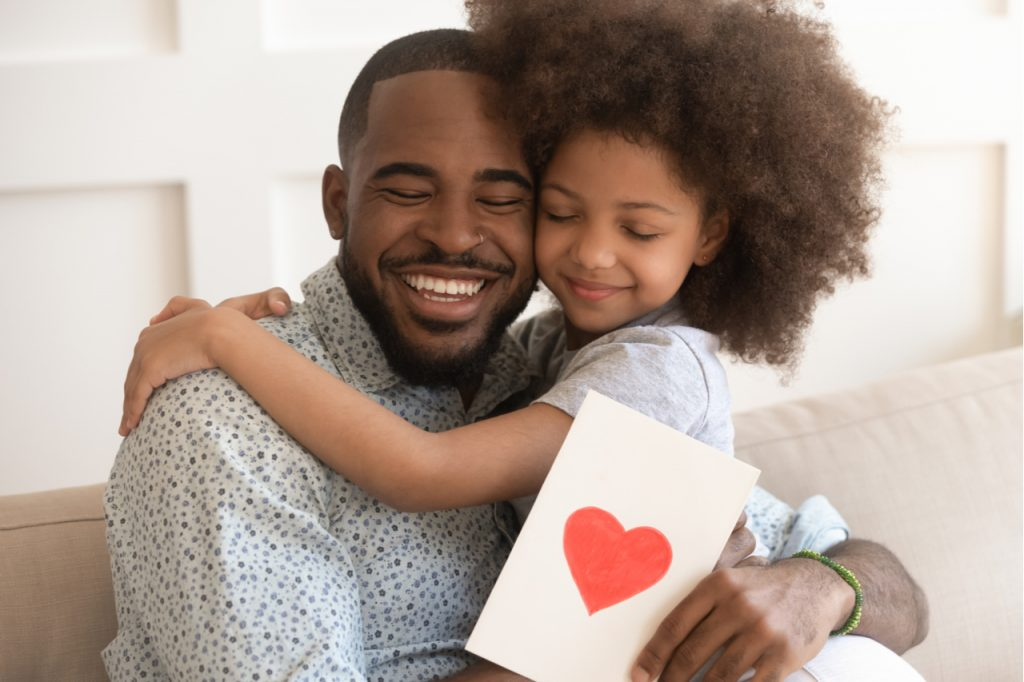 Dad embracing little child daughter holding greeting card with red heart bonding on fathers day concept.