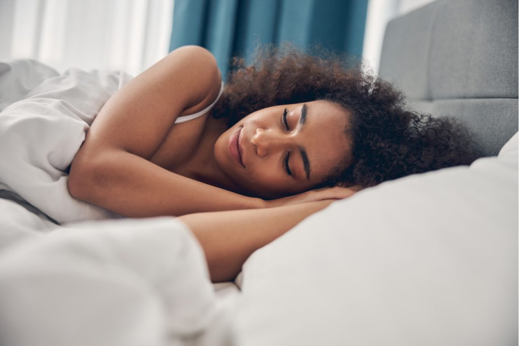 Woman sleeping on one side in bed after taking cbdistillery gummies.