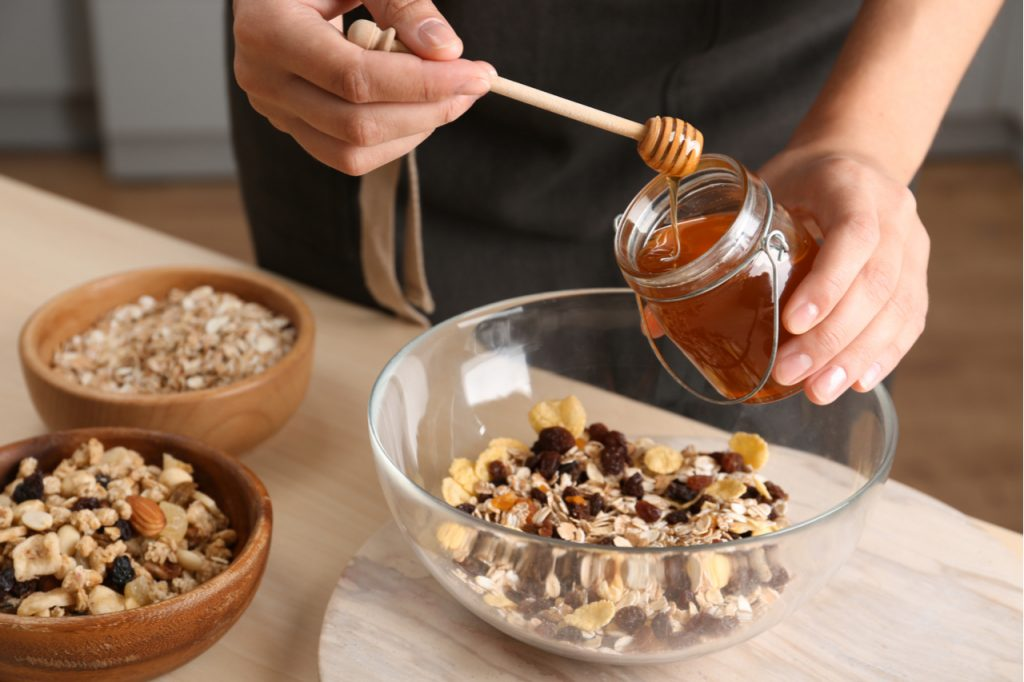 Woman preparing healthy granola bar at wooden table in kitchen.