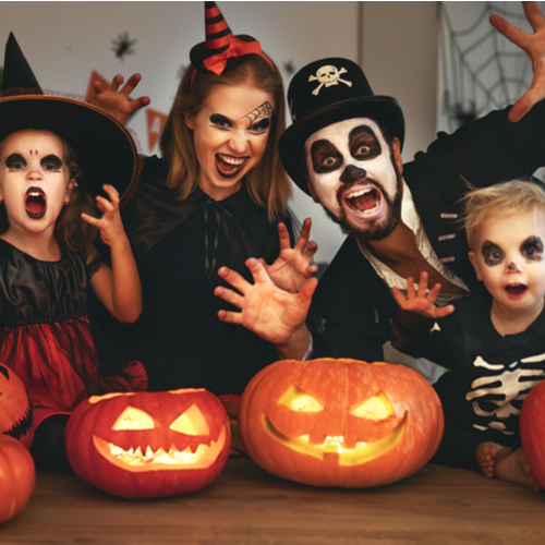 Happy family in costumes and makeup on a celebration of Halloween.