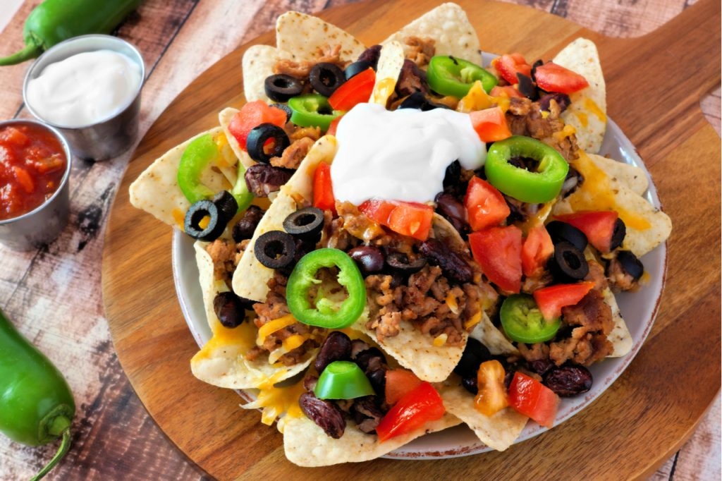 Nacho chips topped with sour cream, ground meat, jalapenos, tomatoes, beans and melted cheese on a wooden paddle board.