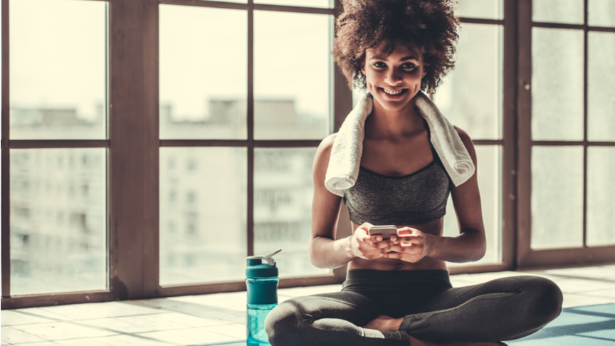 Woman in sportswear is using a smart phone, looking at camera and smiling while sitting on yoga mat.